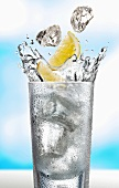 Ice cubes and lemon wedges falling into a glass of water