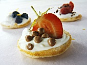 Blini with crème fraîche, strawberry and chocolate dragees