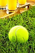 A tennis ball in grass, tray of orange juice behind