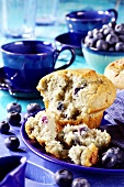 Blueberry muffin, blue coffee cups and fresh blueberries