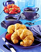Two croissants, two cups of coffee and fresh strawberries