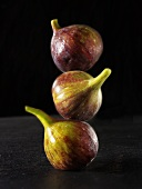Three fresh figs, in a pile, one on top of the other