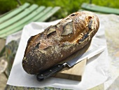 Bread and bread knife on a table in a garden
