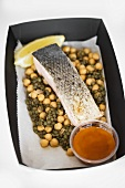 Salmon on chick-peas and lentils in cardboard container