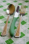 Knife, fork and spoon on checked tablecloth