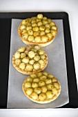 Three gooseberry tarts on baking tray