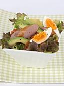 Oak leaf lettuce with avocado, sausage and egg