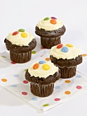 Iced chocolate muffins decorated with chocolate beans