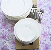 Stacked plates, forks and glasses