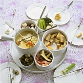 Cheese fondue with vegetables, prawns and bread cubes