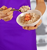 Woman holding a bowl of porridge