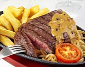 Rump steak with pepper sauce, onions and chips