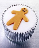 Cupcake with white icing and tiny gingerbread man