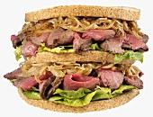Double-decker roast beef, onion and lettuce sandwich