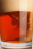 A glass of beer with a lot of head (close-up)