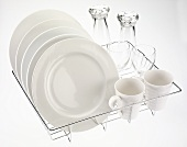 Plates, cups and glasses on dish rack