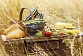 Tisch im Getreidefeld mit Brot, Tomaten, Kürbis und Käse
