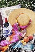 A bottle of red wine, fruit and straw hat on a picnic cloth
