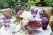 Fresh berries, roses and glasses on table out of doors