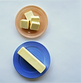 Pieces of butter on coloured plates