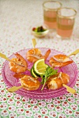 Fried shrimps on cocktail sticks with lime