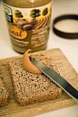 Spreading peanut butter on rye bread