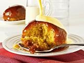 Sponge pudding with strawberry sauce and custard (UK)