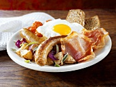 English breakfast: sausages, bacon, egg, potatoes, tomatoes