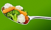 Cauliflower, broccoli and carrots on a spoon