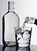 Pouring a glass of vodka, vodka bottle beside it