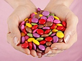 Hands holding coloured Smarties