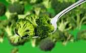 Broccoli florets on a spoon and in background