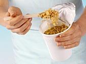 Hands holding instant noodles in plastic pot