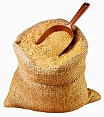 Demerara sugar in jute sack with scoop