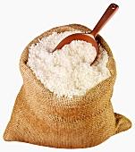 Long-grain rice in jute sack with scoop