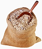 Muesli with rolled oats and nuts in jute sack with scoop