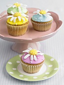 Four cupcakes with daisy decorations on pedestal stand & plate