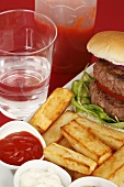 Double burger with chips and dips and a glass of water