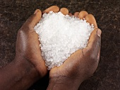 Hands holding coarse rock salt