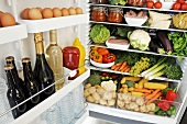Various foods in an open refrigerator