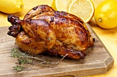 A whole grilled chicken with lemons and sprig of thyme