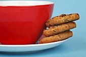 Drei Chocolate Chip Cookies auf einem Unterteller mit Tasse
