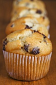Four muffins in a row on a wooden background