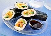Four sushi rolls with soy sauce