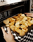 Man taking roast potatoes out of the oven