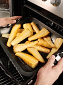 Man taking roasted, halved parsnips out of the oven