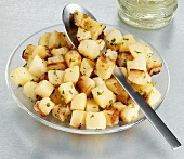 Fried diced potatoes on a glass plate