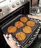 Man taking cookies out of the oven
