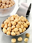 Blanched hazelnuts on a spoon and in a glass bowl