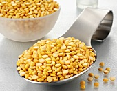 Yellow split peas on a spoon and in a glass bowl
